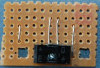 Now insert the light barrier. It will sit atop of the left two wire bridges. Watch out for the letters on the housing, they should be readable from the mounting hole side. Solder one pin on the left, then one on the right, then make a pause of a minute before fixing the remaining ones.
