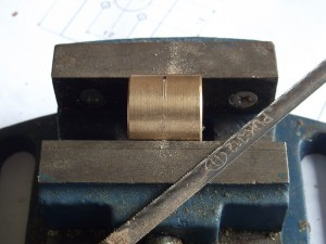 A brass nut marked at half length.