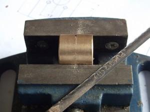 A brass nut marked at half length.